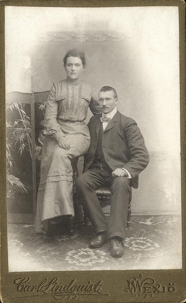 Foto av ett okänt par. Hon är klädd i klänning med hög krage. Han är klädd i kavajkostym med väst, klockkedja och stärkkrage med randig fluga. Helfigur. Ateljéfoto.