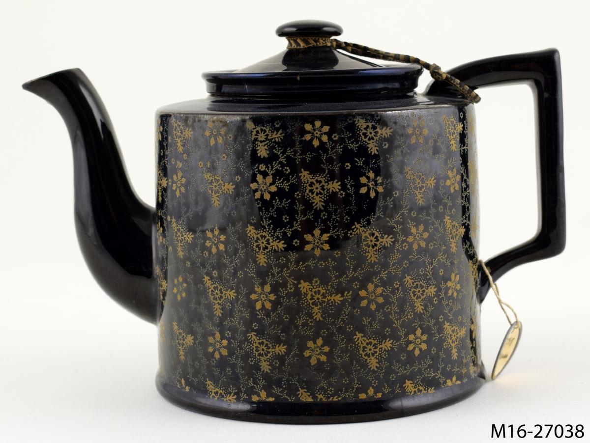 Tekanna, svart med bronserade småblommiga ornament på de vertikala sidorna.