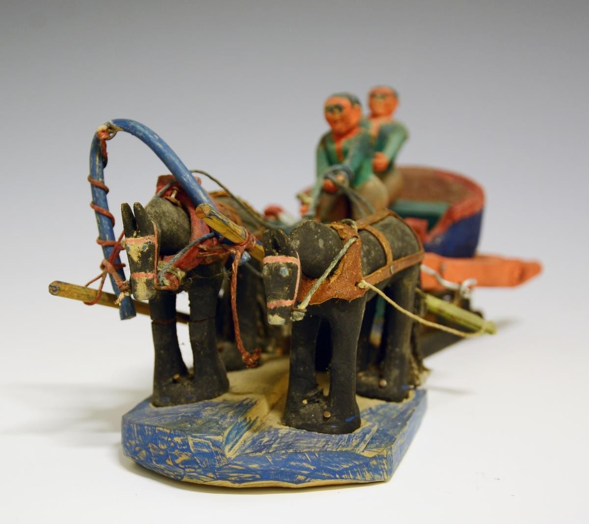 Prot: Leke. Utskåret i tre. Slede med to personer oppi med to hester forspent. Malt i brun, grønn og rød farge.