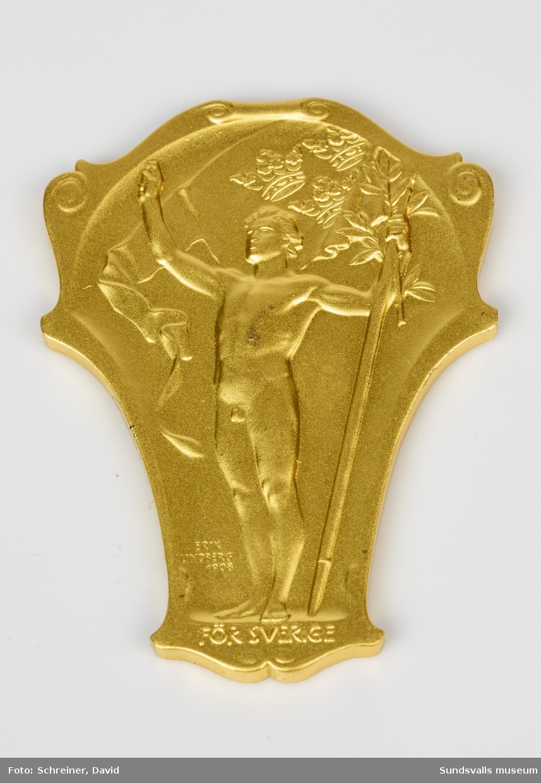 Guldplakett med reliefmönster bestående av en stående man med en vajande vimpel och symbolen tre kronor.