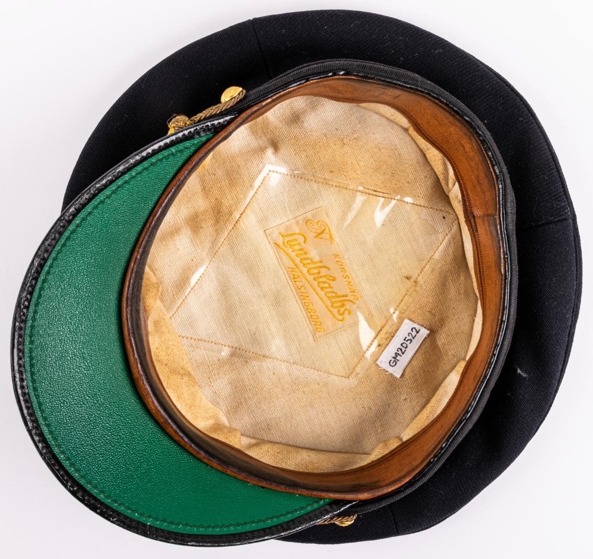 """Skärmmössa m/30 för flygvapnet. Av mörkblått ylletyg (gabardin) med svartlackerad skärm (undersidan ljusgrön). Svart textilband runt mössans nederdel. Kullen cirkelrund, platt och med större diameter. Dess styvnader är borttagna. Flygemblek av broderad guldtråd. Hakrem av flätad guldtråd (m/39), fäst med två små kronknappar. Vitt linnefoder. Svettremmen märkt """"HF"""". etikett i kullen """"KÖRSNÄR Lundbladhs HÄLSINGBORG"""""""