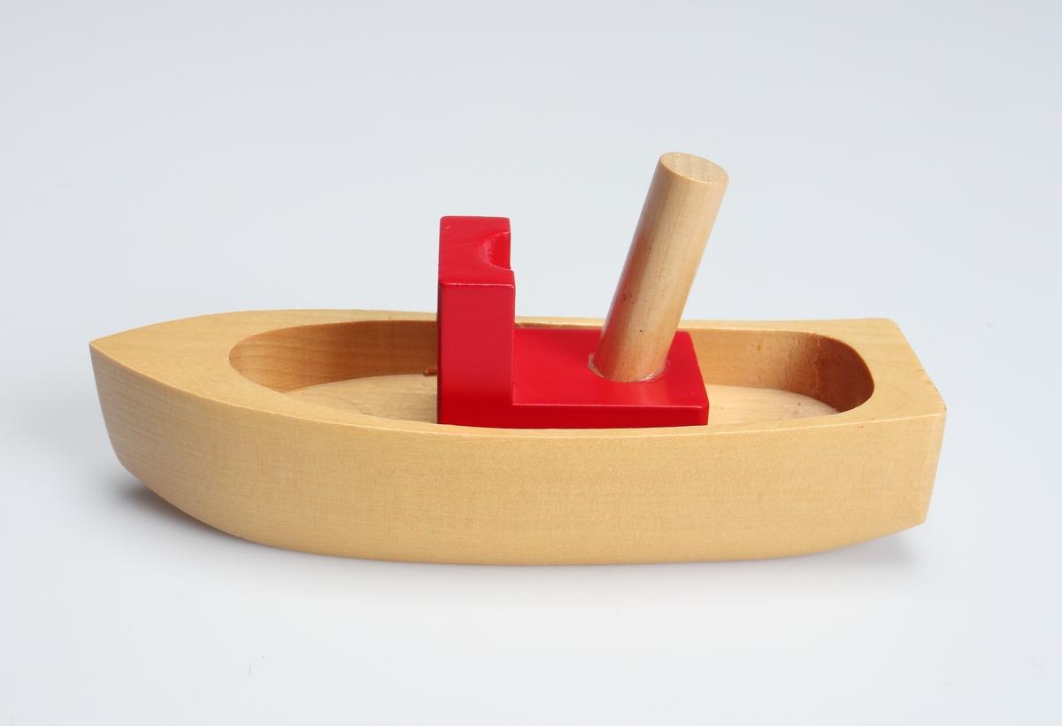 Båt, fernissad och tillverkad ur ett stycke trä samt urfräst inuti. Den är försedd med en rödmålad hytt som har en fernissad skorsten. Den är förpackad i en blå pappkartong med bild på och text på tyska och engelska.