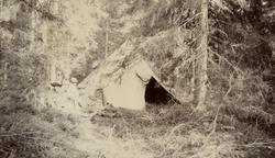 Utanför ett skyddstält i skogen.