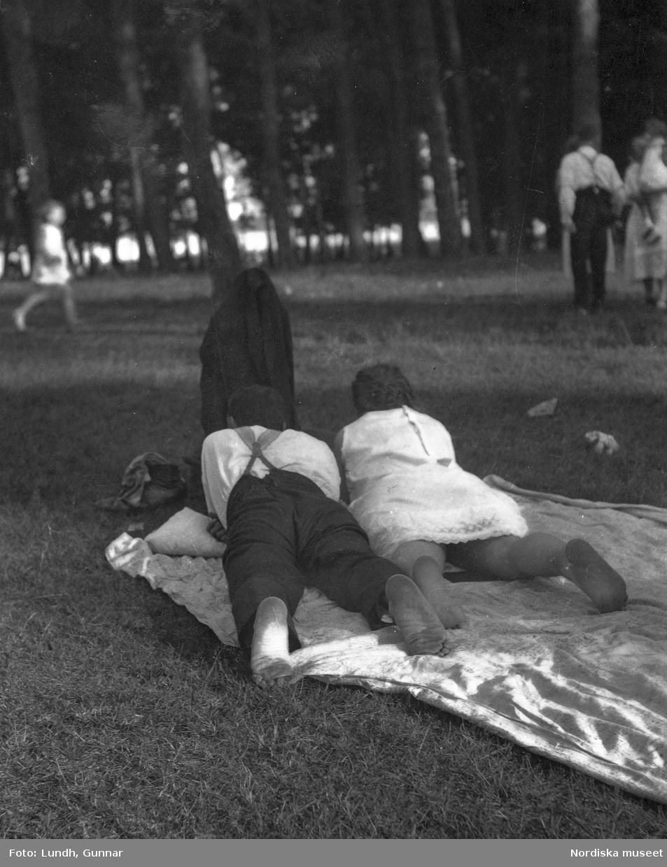 """Motiv: Utlandet, Bad v. Berlin 147 - 156 ; Vy över en badstrand med människor som sitter på marken och människor som badar , en man och en kvinna ligger på en filt i en park, anteckning på kontaktkarta 149 """"Badande barn""""."""