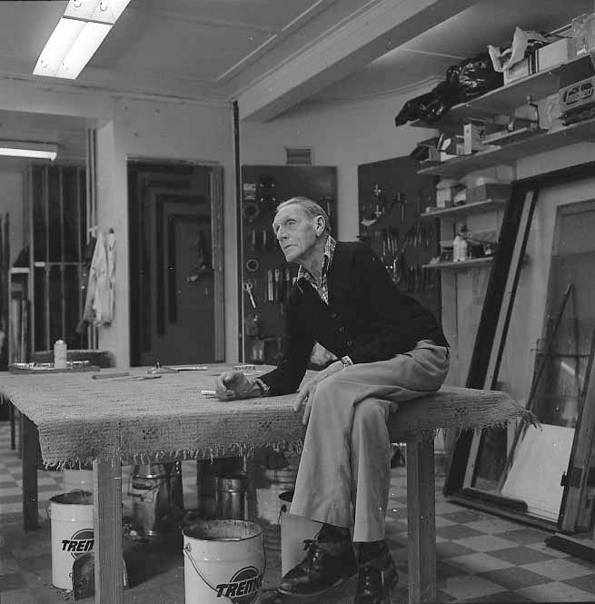 Glasmästare Bernt Rendahl sitter på arbetsbordet i sitt glasmästeri.