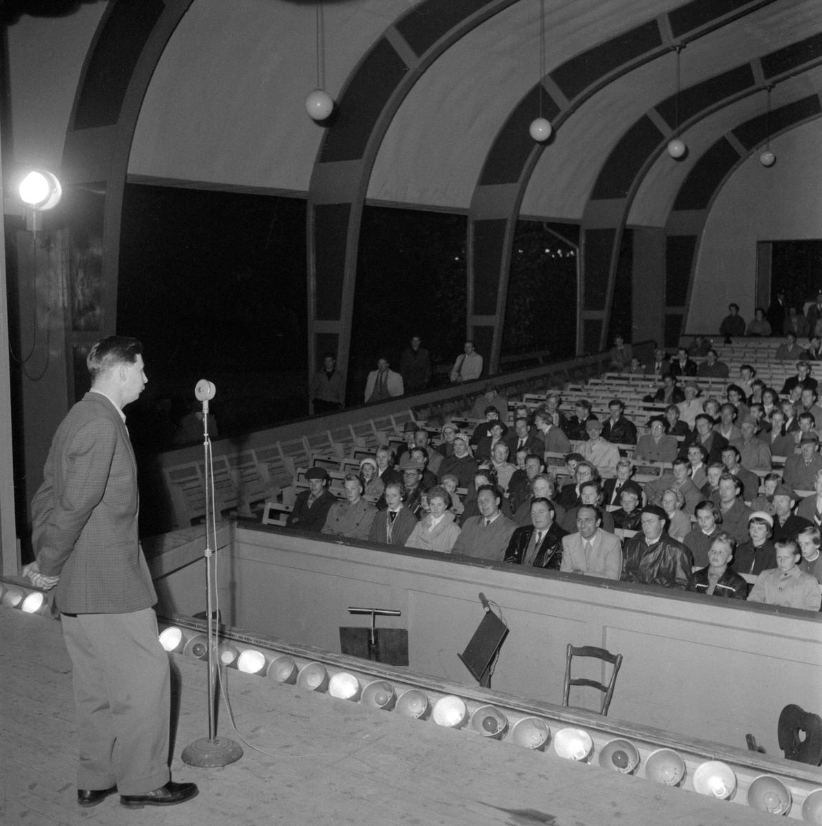 """Gösta """"Snoddas"""" Nordgren under ett uppträdande i Åtvidabergs folkpark 1956. Scenframträdandet var en del av parkens stora festligheter under den första helgen i september. Utöver """"Snoddas"""" uppträdde Sigge Wassbergs orkester från Malmö och Arne Bergelings från Linköping samt akrobatparet Asta och Allan. Hallbergs nöjestivoli erbjöd förutom karuseller även många kontinentala nöjesanordningar. Dessutom sägs hela nöjesfältet varit i sagolik belysning."""