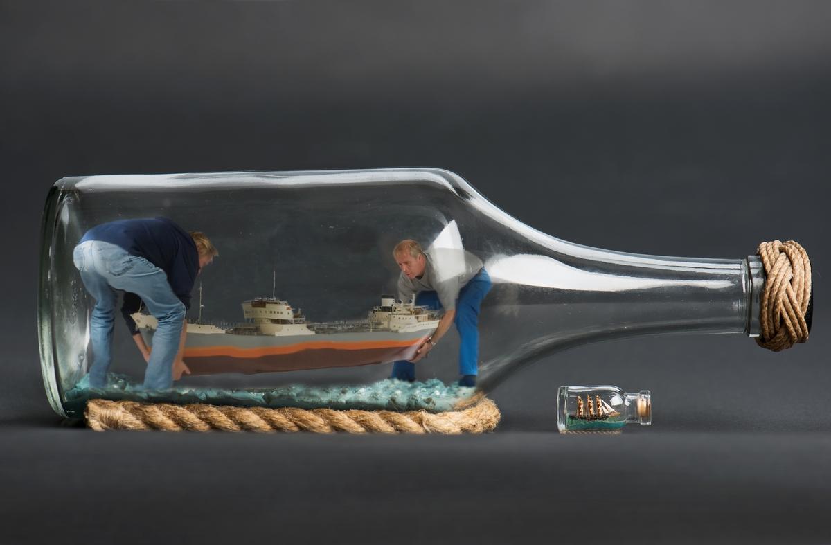 Sjöhistoriska museets modellbyggare Jan Claesson och Stefan Bruhn med en flaskskeppsmodell. Bearbetad bild.