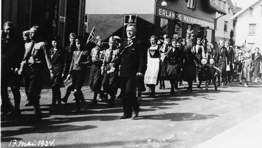 17. mai tog 1934 i Storgata mellom L. Bellesen og H. Bellesen sine eigedomar. Læraren fremst er Ola Barkved.