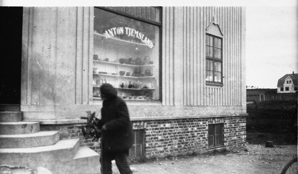 Pinn-Ola framfor forretninga til Anton Tjemsland. I bakgrunnen huset til Gudrun Natvig (eigar frå 1940).  Denne samlinga er ein del av gamle bilete som Jens Erland fann i uthuset der han dreiv keramikkverkstad ei tid. Anne Marie Time eig no originalbileta og har vore informant. Ingolf Time var hennar farbror.