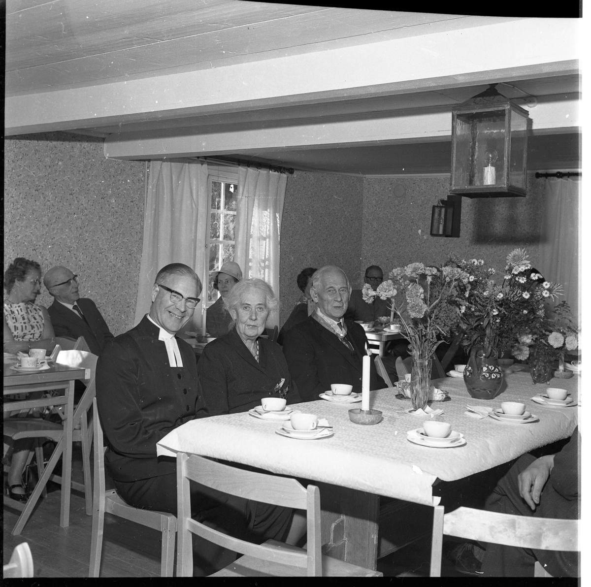 Äldre män och kvinnor sitter vid dukade kaffebord, troligen i en församlingsgård. Intill kyrkoherden sitter paret Anna och Rudolf Boman. Den senare har tilldelats medalj.