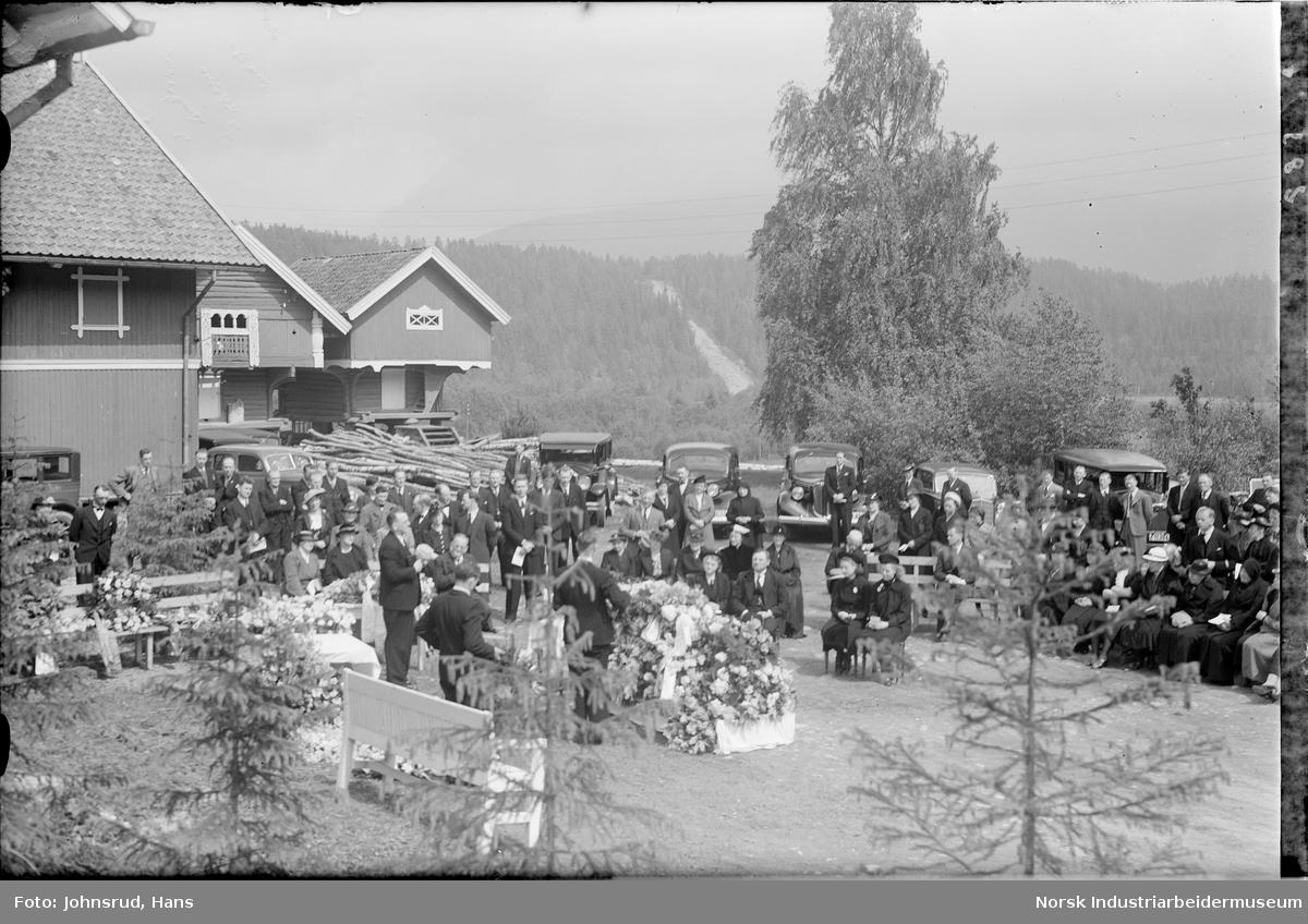 Begravelse på gårdstun. Mennesker i pentøy står rundt blomsterdekket kiste. Biler i bakgrunnen.