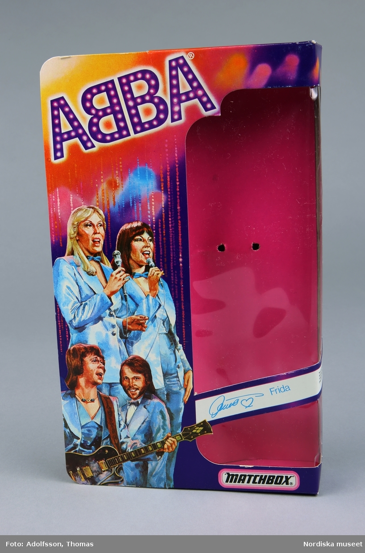 a-d) Fyra kartonger av papp och celofan, försedda med bilder av popgruppen ABBA samt namnteckningar av de fyra medlemmarna. Det enda som skiljer kartongerna åt är att var och en har en etikett med förnamn och namnteckning på den ABBA-medlem som dockan föreställer. På baksidan av kartongen finns text på fyra språk; engelska, svenska, tyska och spanska som uppmanar till samlande av dockor och scenkläder.