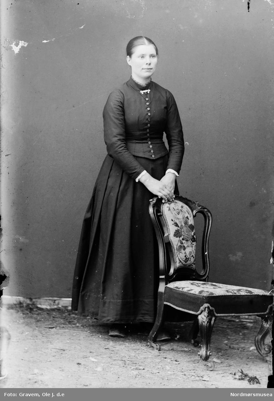 Portrett av kvinne stående bak stol i helfigur.
