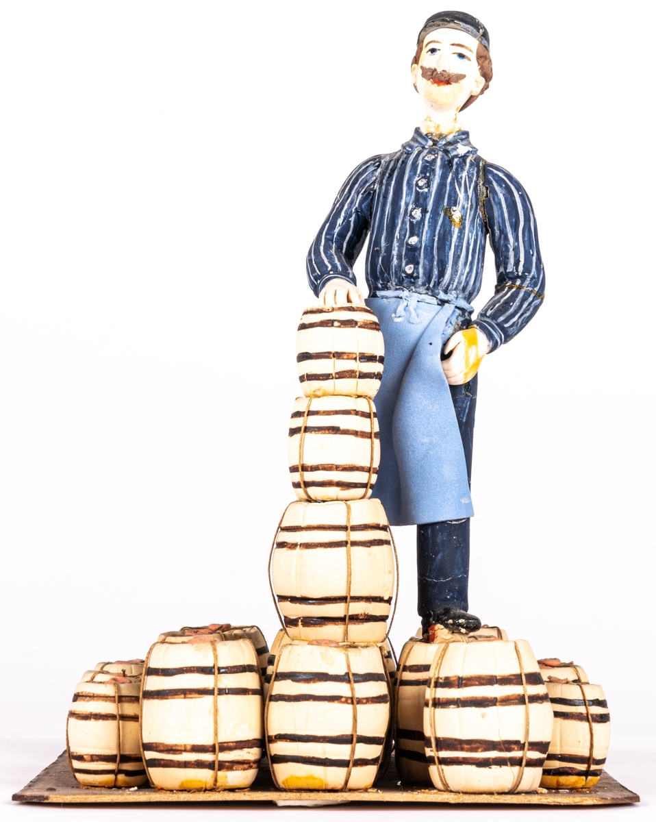 Modell av sockerpasta och papper, dekormålad. Modellens bas byggd av papp, klädd med små tunnor tillverkade av sockerpasta.  Katalog: Modell. en man stående på en samling snuskaggar.  Katalogkort: Modell av gips, målad, visade en man stående på ett lager av 13 större och 9 mindre förseglade snuskaggar. Kaggarna stå på horisontellt underlag, alla utom fyra som är upptornade på varandra.