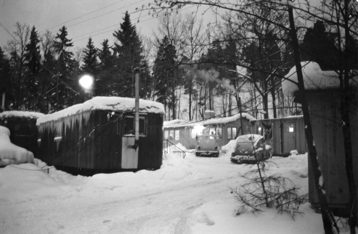 """Romskt läger i Ekstubben 1963. Lägerplatsen låg i Skarpnäck söder om Stockholm, i nuvarande Flatens naturområde, på en plats där det i dag ligger en motorbana. Lägret var samtida med Skarpnäckslägret några kilometer bort och iordningställdes 1959 av Stockholms stad för svenska romer i kommunen som ännu inte hade fast bostad. Ekstubben stod färdig för inflyttning 15 mars 1960. För drygt 50 år sedan var Ekstubben och Skarpnäckslägret i fokus för Katarina Taikons kamp för att romernas rättigheter, men i dag är det få personer som känner till dem och vet var lägren legat.  Bilden är tagen i samband med reportaget """"Vagabond eller vanlig människa?"""" av Roland Hjelte och Karl Axel Sjöblom som sändes i SVT i mars 1963. Reportaget skildrar livet i lägren i Ekstubben och Skarpnäck under vintern 1963. I intervjuerna med de boende i lägret framhålls det akuta önskemålet om fast bostad. I lägret bodde det året 15-20 familjer och reportern berättar att människor har bott här flera år i väntan på att Stockholms stad ska lösa bostadsproblemet. Det är vinter, snön har fallit och vissa nätter går temperaturen under nollstrecket inne i husvagnarna. En man berättar att han är uppe hela nätterna för att elda i kaminen. Han säger till reportern: """"När alla andra fått bekvämligheter ska vi också ha det. Vi kan inte ha det så här!"""".  Fastighetskontoret i Stockholms stad hade i en kommunal utredning 1955–1957 kommit fram till förslaget att iordningställa särskilda lägerplatser. Lägren skulle finnas under en övergångsperiod innan fasta bostäder ordnats, men i realiteten drog bostadsfrågan ut på tiden och lägren blev kvar i fem år. I Ekstubben bodde människor under enkla förhållanden, inledningsvis i tält och vagnar och efter hand också i egenbyggda baracker och stugor kring en öppen yta. Lägret försågs med el och vatten, torrtoaletter samt sophämtning.   Det skulle dröja till maj 1964 innan de sista av de svenska romerna flyttade från Ekstubben. Senare användes Ekstubben dock fortsatt som läge"""