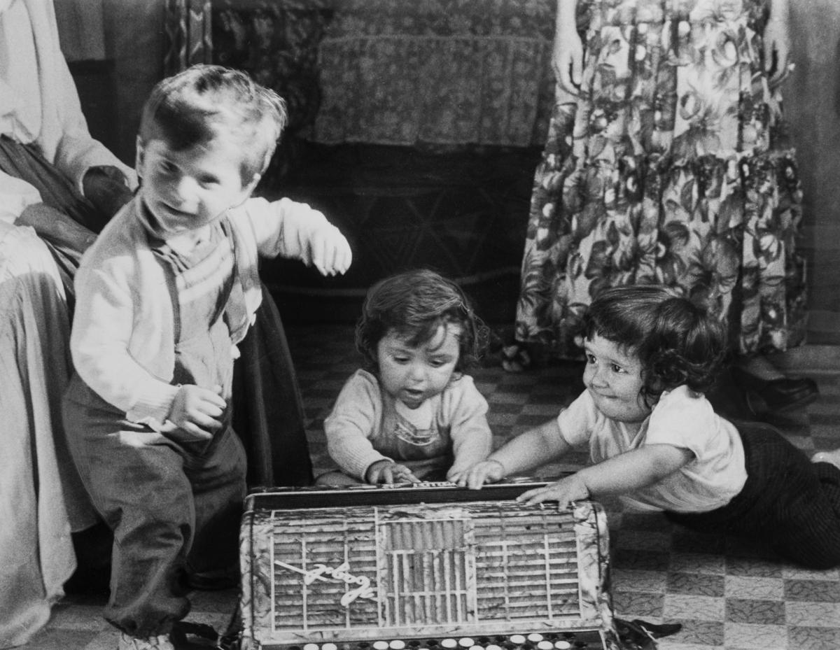 """Trots att Sverige haft skolplikt sedan 1842 har inte alla barn haft rätt att gå i skolan. Redan 1933 skrev Johan Dimitri Taikon till skolöverstyrelsen och bad om skolundervisning för romska barn. Först tio år senare blev Dimitri Taikon hörsammad då han tillsammans med den frikyrkligt engagerade Otto Sundberg blev beviljad 1500 kronor för att starta en """"försöksskola"""" vid lägret i Lilla Sköndal, Gubbängen i Stockholm. Denna verksamhet kom senare att drivas för Stiftelsen Svensk Zigenarmission, grundad 1945, som drev sommarskola för romska elever under hela 1940- och 1950-talen. Eleverna var mellan 6 och 60 år och satsningen blev mycket medialt uppmärksammad. Efter en tid med olika former av försöksverksamhet föreslog  """"Zigenarutredningen"""" (1954), den första """"invandrar- och integrationsutredningen"""" i Sverige, att romer skulle gå i vanliga skolor. Frågan om undervisningens organisering fick de enskilda skolorna att hantera på egen hand men från och med juni 1960 fanns möjlighet för kommuner att rekvirera bidrag från staten för speciell undervisning av romska barn. Först efter att alla romer fick bli bofasta på sextiotalet, fick samtliga romska barn möjlighet att gå i skola året om. Bilden är tagen vid en skolavslutning av en ambulerande skola. Tre pojkar leker med ett dragspel."""