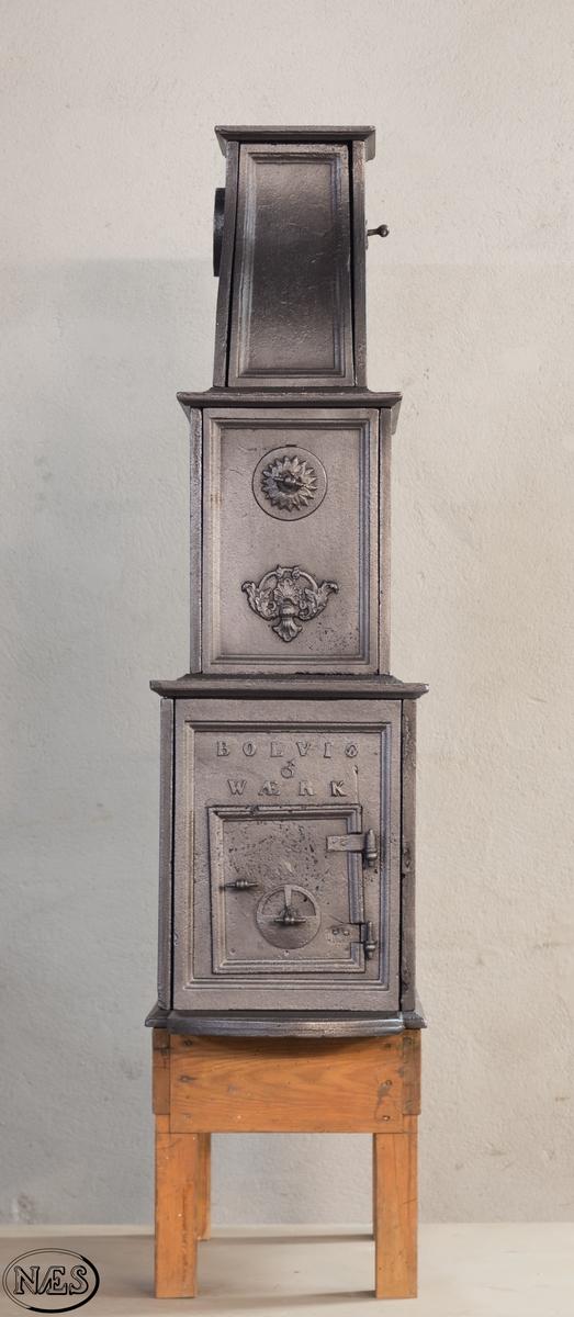 Etasjeovn med svunget topp. Ovnsdør med ventil på kortside. Alle ovnsplatene er rammet inn med en enkel profilert list ytterst på ovnsplaten. Hovedmotivet på langside 1.etg. - En lyre med en griff på hver side stående på en sokkellist. Ovnen er oppover i etasjene dekorert med blomsterdekor/ rosetter og utskjæringer. 2. etg har en buet gjennomgående åpning. Toppen har en halvrund gjennomgående åpning.