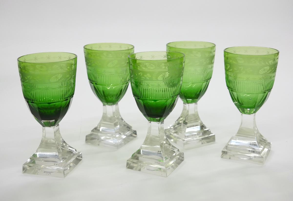 Vinglas med cuppa av grönfärgat glas av stympad äggform, med graverad kantbård och dekor i skärslipning. Fyrkantig fot av ofärgat glas.