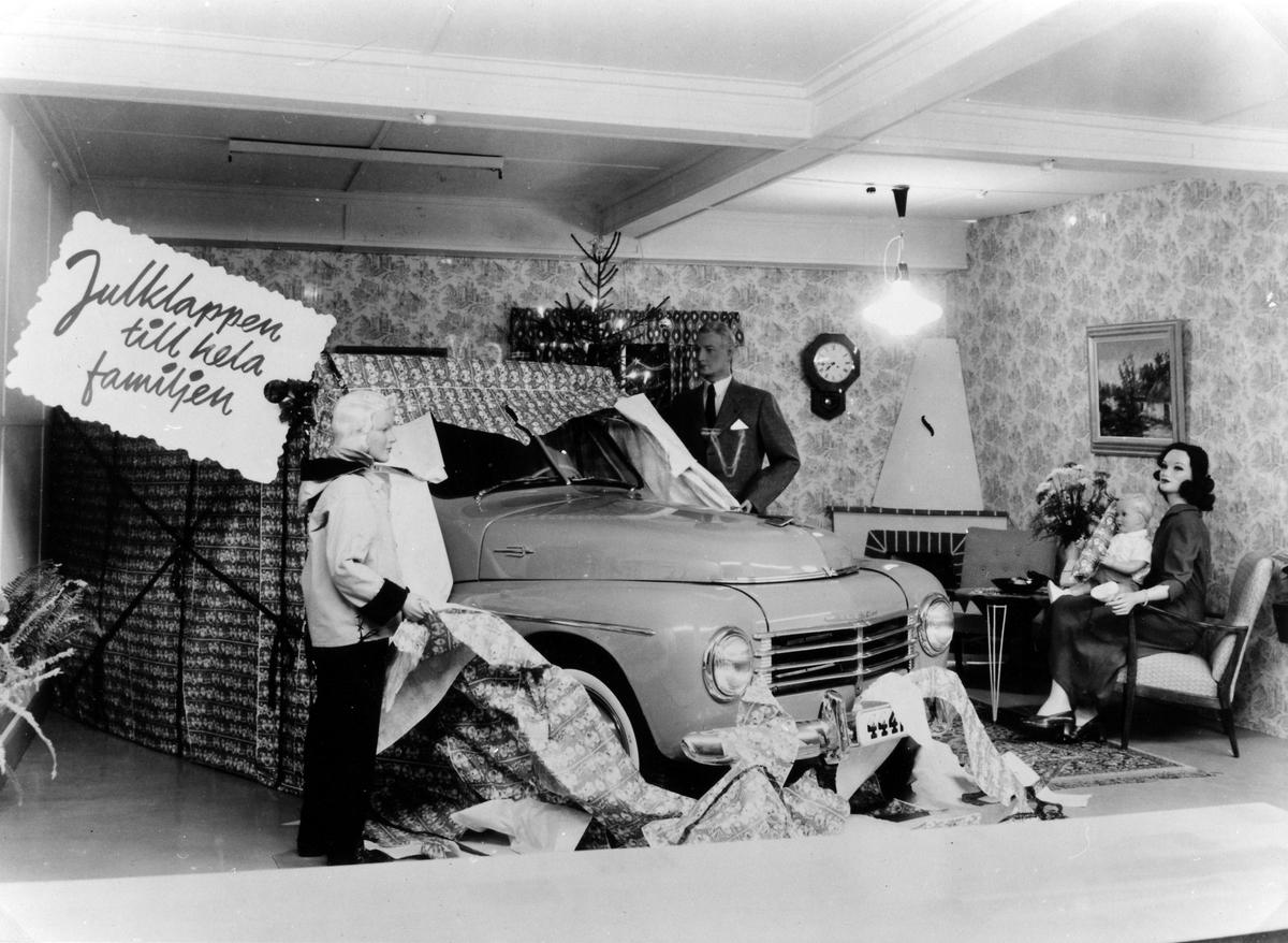 Alingsås Bil- och motorverkstads julskyltning i en, troligtvis hyrd lokal, i kv. Storken 5, ca 1955. Skyltodockor i en tidstypisk hemmamiljö, kvinna i fåtölj med barn i knäet, man som öppnat ett stort paket med inslagen volvobil och pojke som nyfiket tittar på från andra sidan.