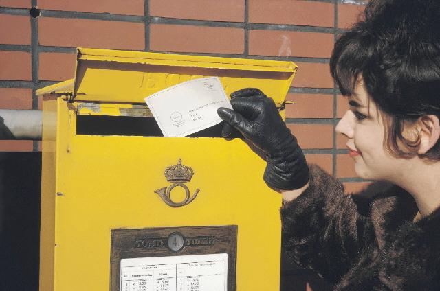 En dam - i en arrangerad situation - postar en portofri försändelse till För-lagshuset Norden AB i Malmö.