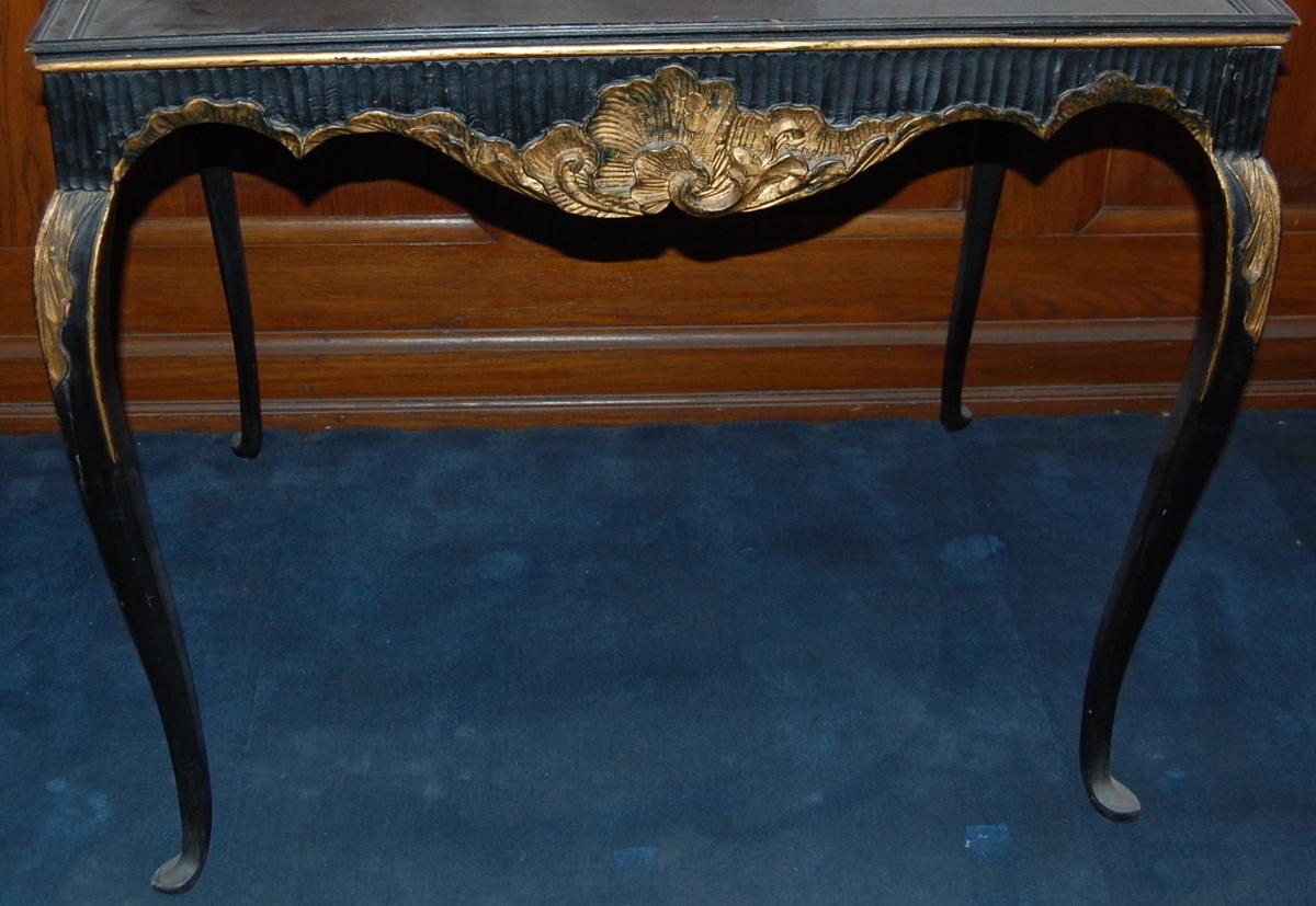 Sargene av bjerk, bena og platen av furu. Sargene utskåret med rocailler og rifler, bena med bladornament øverst. Sortlakkert med forgylte ornamenter.