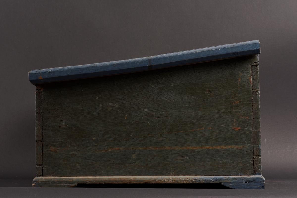 Rektangulärt skrin med lutande pulpetlock tillverkat av ek. Skrinet är blåmålat, men har ursprungligen varit grönt. På kanterna senare bättringsmålat med blå färg. På locket en målad rokokokartusch, i den ditmålade initialer, MJD, samt årtalet 1806. Inuti ett fack, läddika, utan lock. Nyckel och låsbeslag saknas.