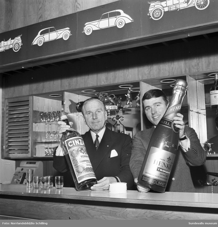 Gunnar och Bo Wilöf poserar i baren på Knaust med varsin jätteflaska.