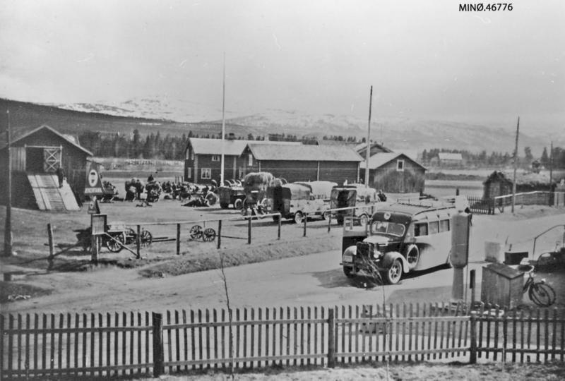 Fra Grimsbu, med tyske styrker som var på vei fra Nord-Østerdalen til oppsamlingsleir i Oppdal midt i mai 1945. Til høgre ses bensinpumpa der følget med kongen fylte bensin under flukten gjennom distriktet lørdag 13. april 1940. Foto: Anno Musea i Nord-Østerdalen, 46776.