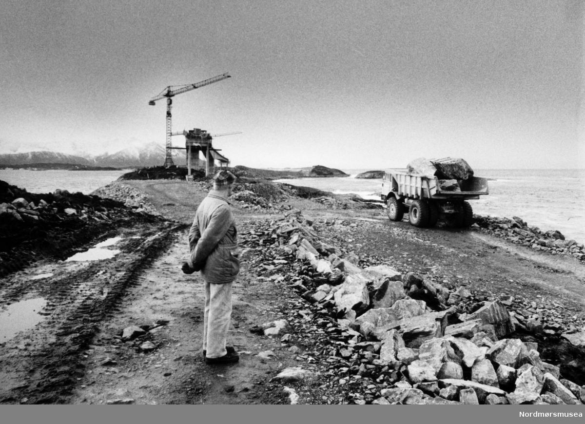 """Fra byggingen av Atlanterhavsveien mellom Averøy og Eide i Møre og Romsdal. En veistrekning på 8.274 meter. Anlegget består av åtte broer på til sammen 891 meter og går over holmer og skjær. Veien kostet 122 millioner i 1989 og var delvis bompengefinansiert. Anlegget ble åpnet 7. juli 1989 og bommen ble fjernet i juni 1999. Atlanterhavsveien er landets åttende best besøkte naturbaserte turistattraksjon (2004) med 283.500 besøkende. Veistrekningen er foreslått vernet i """"Nasjonal verneplan for veger, bruer og vegrelaterte kulturminner."""" (Kilde: Wikipedia Norge). Bildet er fra avisa Tidens Krav sitt arkiv i tidsrommet 1970-1994. Bildet er fra avisa Tidens Krav sitt arkiv i tidsrommet 1970-1994. Nå i Nordmøre museums fotosamling."""