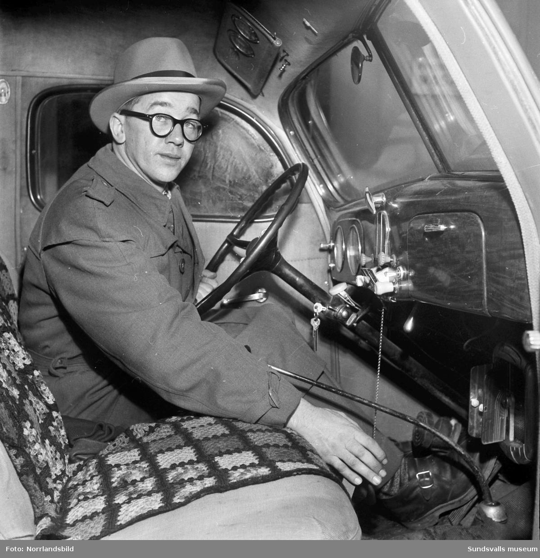 En man i en lastbilshytt med reglage för automatiska snökedjor.