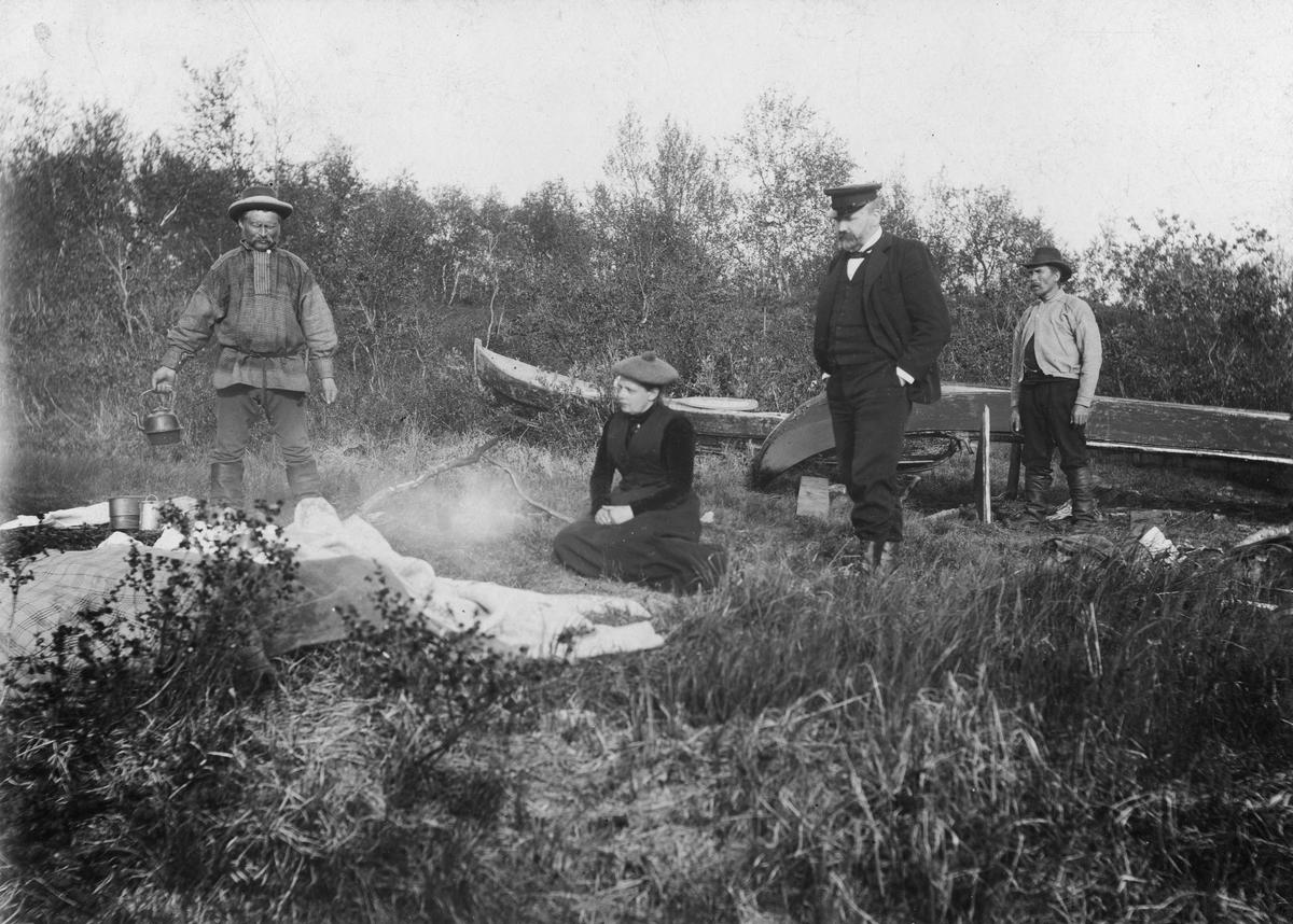 Ekteparet Wessel på utflukt. Sittende midt i bildet Ellisif Wessel, stortingsmann Håkon Finstad står ved siden av henne. To ukjente menn er også med, til venstre sannsynligvis vappusen - kjentmannen holder på å koke kaffe. Ukjent sted, sannsynligvis langs Pasvikelva ca år 1900.