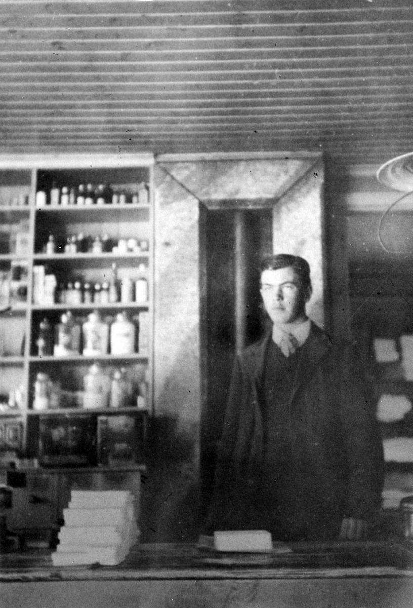 Bodbiträdet Wahlström står bakom speceridisken i Claes Nygrens affär. Bakom honom syns hyllor fyllda med flaskor i olika storlekar.