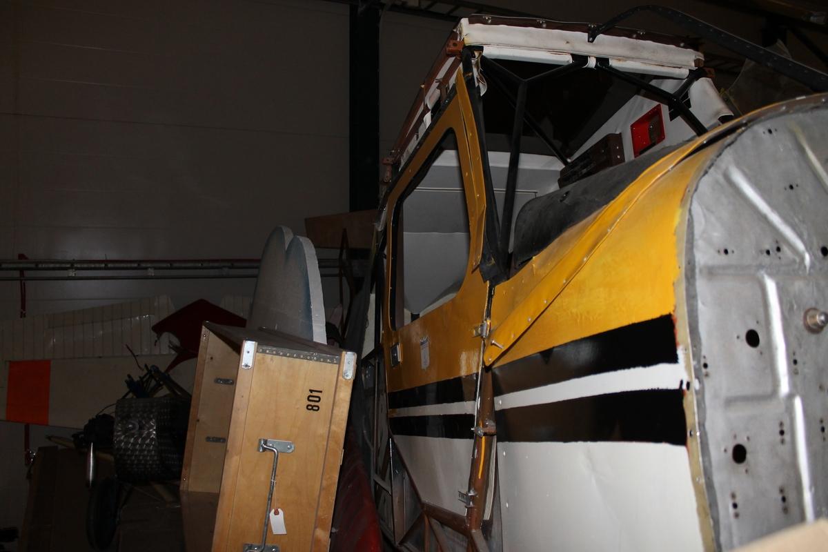Flygplan i havererat skick. Propellerflygplan av modell Bellanca Decathlon. Flygkropp, vingar och utrustning är separerade. Gulmålat.