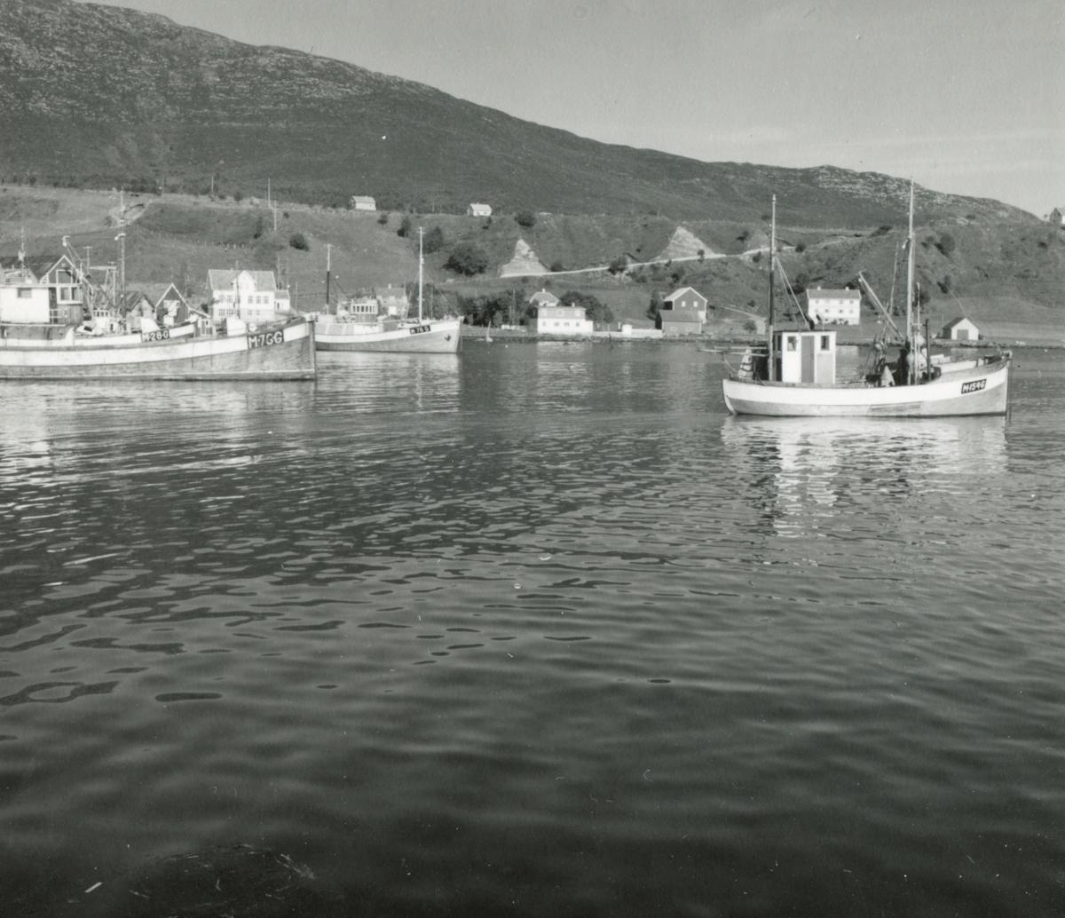 Prospektfotografi med oversikt over havna med båter og fiskebruk på Godøy, Giske.