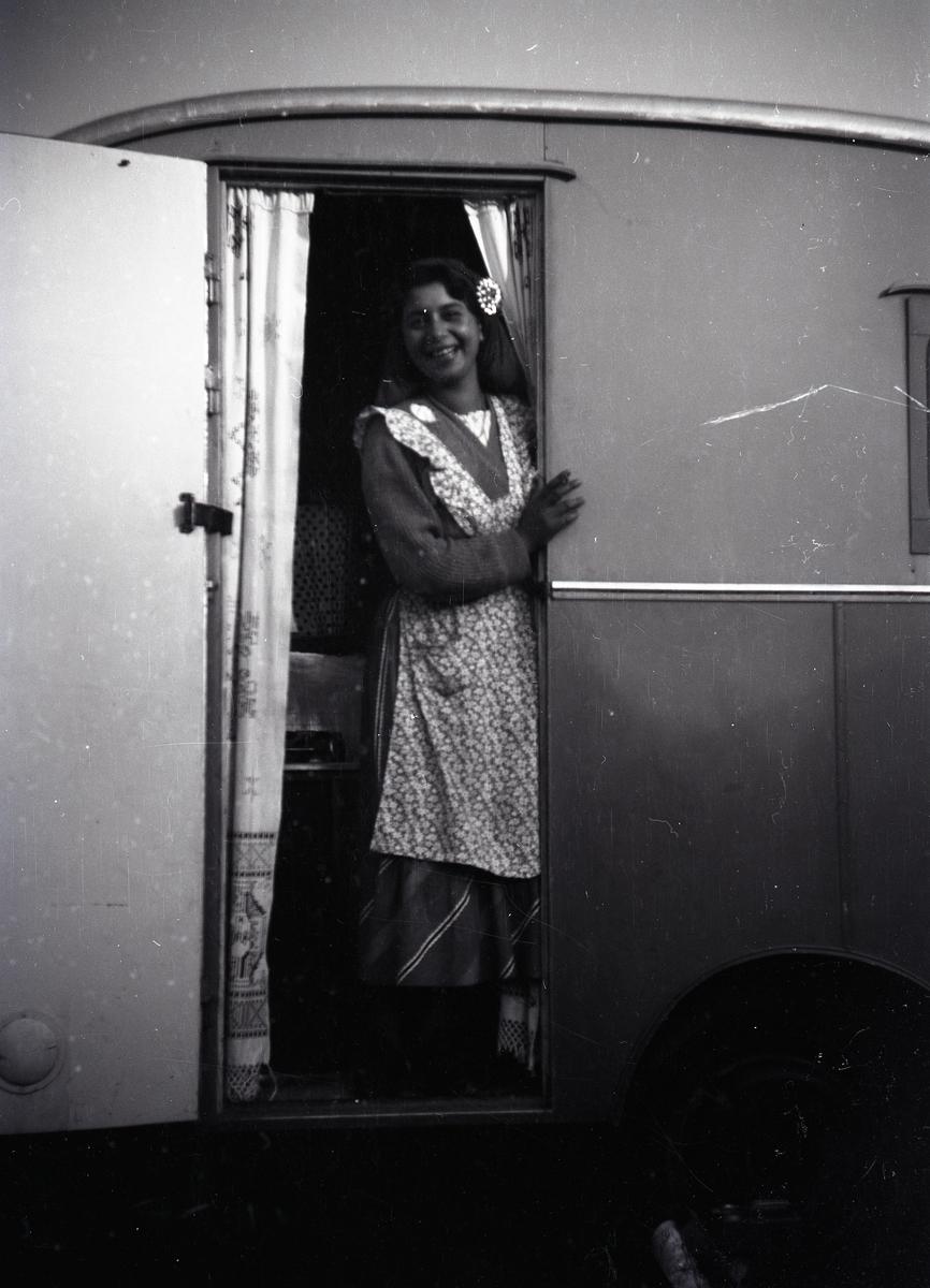 En ung kvinna står i dörren till en husvagn och skrattar mot fotografen. En stor del av Europas romer mördades i Förintelselägren under nazisternas folkmord, men kvinnan på bilden är en av de två överlevande kvinnor som lyckades ta sig till Sverige efter kriget. Under nazismen utpekades romer som syndabockar för majoritetssamhällets motgångar. I en del ockuperade länder mördades romer i massavrättningar, medan de på andra håll tvångsförflyttades till koncentrations- och utrotningsläger.