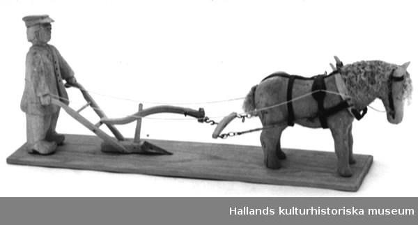 Man med häst, spänd framför ett potatisårder. Allt utskuret i trä. Figurerna fastsatta på en rektangulär träplatta.