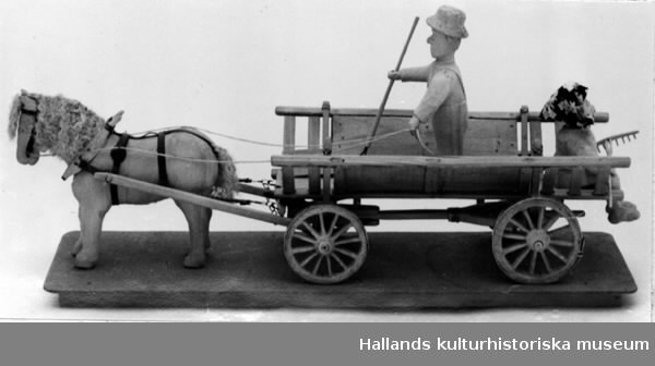 """Skulptur av trä. En häst dragande en """"läddevagn"""" i vilken en man, som håller i en räfsa, sitter. De utskurna figurerna fastsatta på en rektangulär masonitplatta."""