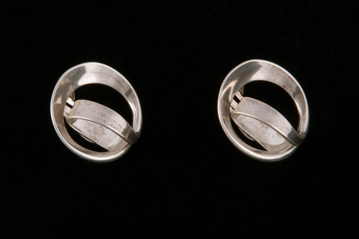 Blankpolerte øreklips av flathamret sølvbånd av varierende bredde. Bøyd i sirkel og ført ned i en løkke inne i sirkelen der endene er loddet sammen.