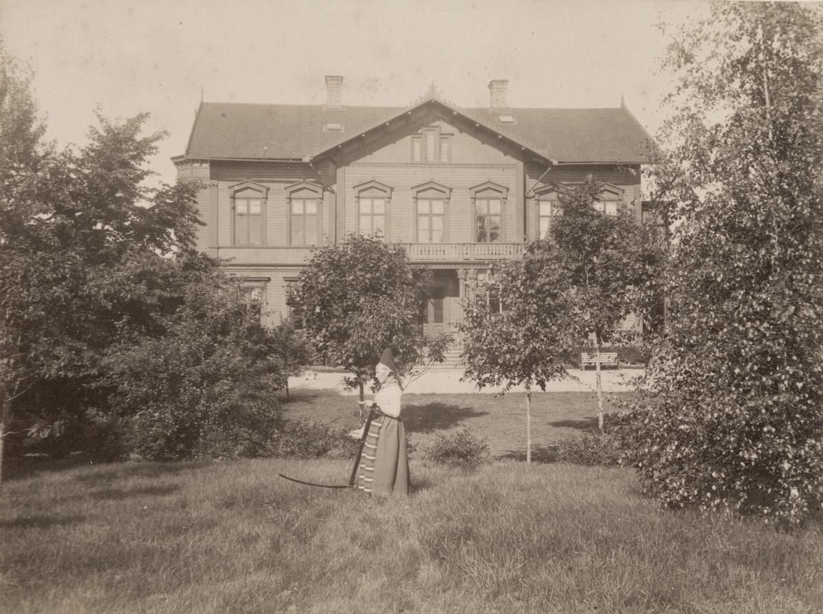 Villa Rettig sedd från sidan. I trädgården står en trädgårdskulla som håller i en lie.