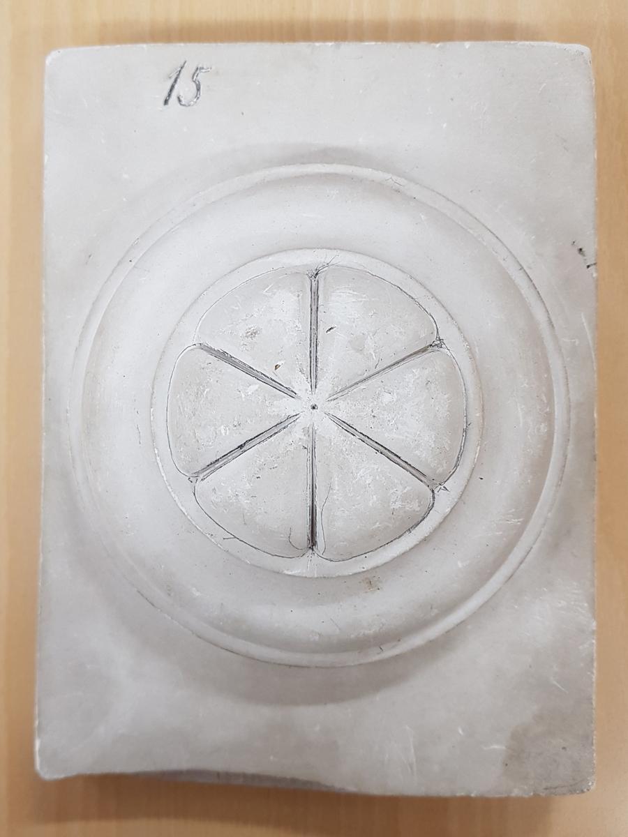 Rektangulär gipsavgjutning med ett runt mönster i relief.  Ingår i en samling använda i teckningsundervisning för teckning av skuggverkan m.m. Avgjutningarna visar blomsterrankor, druvklasar, blommor, halvklot, valv, kolonnhuvud m.m. Storleken på avgjutningarna varierar från medaljonger med diam. 14,3 cm. till block med storleken 25x38 cm.  Två av avgjutningarna är signerade av olika tillverkare, en av ''Tognarelli Stuttgart'' och en ''Eigenthum von J.F.T. Holmberg Altona''. Avgjutningarna är armerade med trä samt försedda med metallöglor för upphängning. En avgjutning har avslaget hörn och en har en genomgående spricka.  Avgjutningarna upptäcktes i Januari 1995 i källaren på f.d. Vänersborgs Flickskola. De låg packade i en trälåda fylld av träull.
