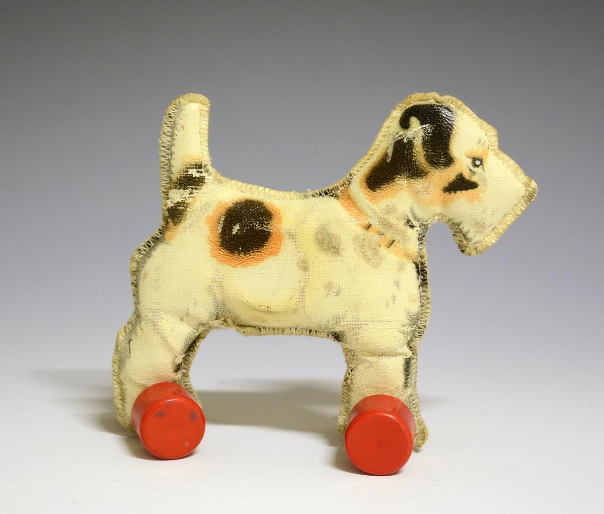 Hund med sikk-sakk søm rundt. Røde hjul av plast festet til beina.