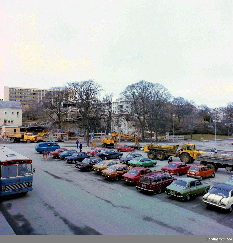 Nerparken 1977. serie.  Bussen til flyplassen avgår fra Braaten SAFE kontor i Tinghuset. Til vestre på bildet ses en buss fra Kristiansund Frei Billag. Selskapets busser var lakkert i grå-blå med rødt tak og gule felt rundt vinduene. Denne bussmodellen ble levert ca. 1970-1974 og viser at bildet ikke er tatt før 1970. (info:  Sveinung Berild)   -Foto fra parkeringsplassen på Kongens plass på Kirkelandet i Kristiansund, hvor vi i bakgrunnen ser pågående arbeid i det som i dag er Sparebank1 Nordvest sin tomt i Langveien 21.  Fotograf er Nils Williams. Fra Nordmøre museums fotosamlinger.
