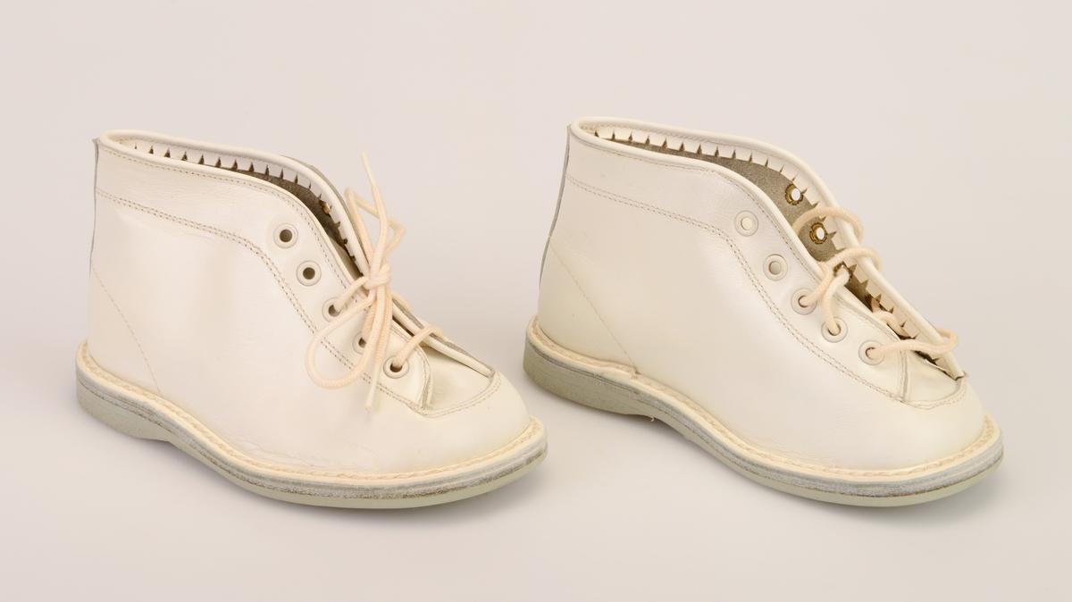 Et par barnesko i størrelse 23 i skoeske med silkepapir. Skoene er i hvitt skinn med lysegrå såle av kunstlær. De er randsydde. I front er det 5 par hull med maljer for snøring. Under snøringen er det en enkel tunge av hvitt skinn. Skoene har hvite, runde skolisser. Det er sømdekor på skoene. Langs kanten innvendig er det en takkete kant. Skoene ligger i en skoeske av papp som er stiftet sammen. På den ene kortsiden er det trykt på fabrikkens navn, varemerke og logo samt artikkelnummer og størrelse. Logoen er en sirkel med en Nord-pil igjennom. Skoene er ikke brukt.