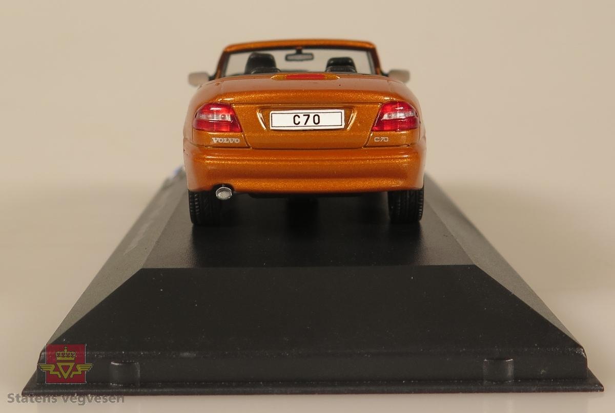 Oransje plastbil som står festet på en svart plast sokkel. Innpakket i en blå pappeske.