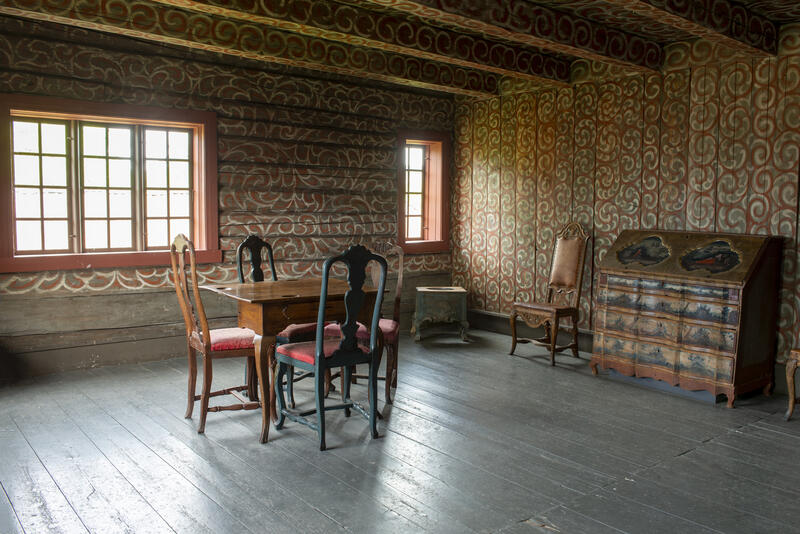 Interiør fra Bolstadbygningen viser en stolgruppe og en kiste i et rom med dekormalte tømmervegger. (Foto/Photo)