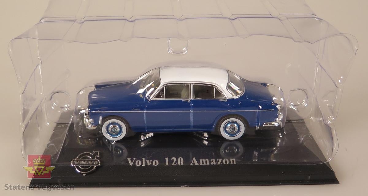 Primært blå og sekunært hvit plastbil som står festet på en svart plast sokkel. Innpakket i en blå pappeske.