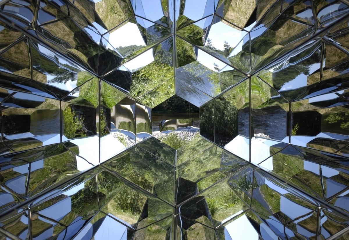 """Viewing Machine er et stort, praktfullt kaleidoskop som man kan se inn i. Kaleidoskop er et optisk apparat som gjør det mulig å se speilbilder av speilbilder med stadig nye mønstre ettersom man vender på det. Viewing Machine gir stadig nye opplevelser av omgivelsene rundt den når man beveger på den ved alle de speilflatene inne i """"kikkerten""""."""
