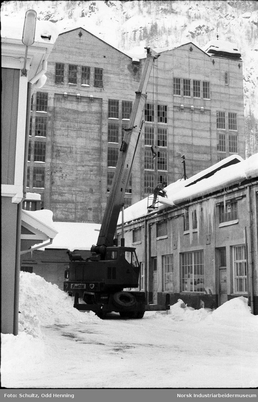 Folk som rydder snø på takene på fabrikkbygning med hjelp av en lift.