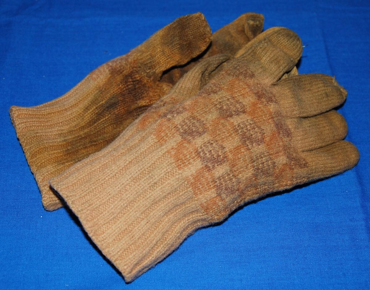 Ett par stickade fingervantar med rutor på handloven i svart. Orangbrun färg i övrigt.