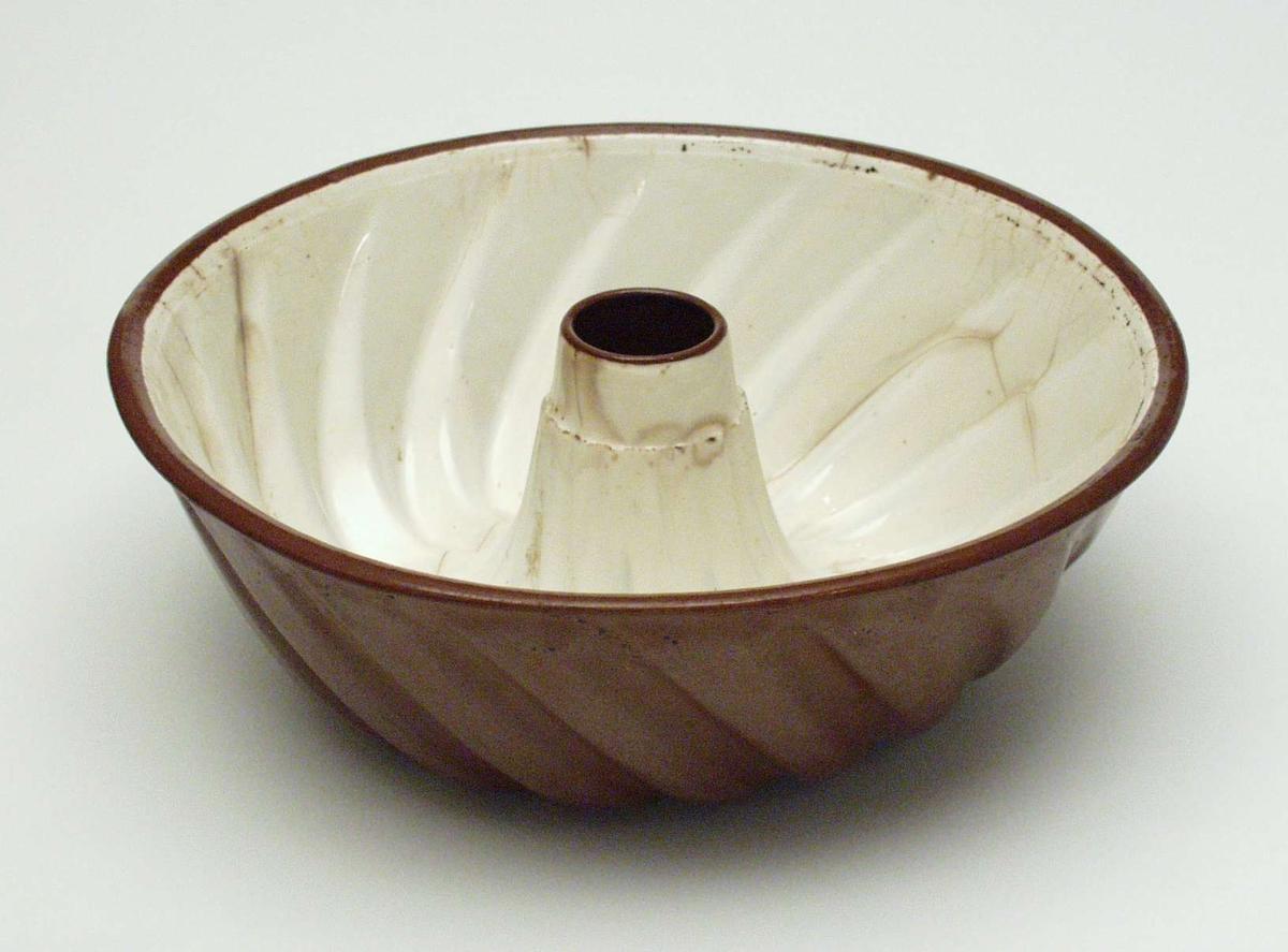 Puddingform i keramikk. Den er beige innvendig og brun utenpå. Glasuren er krakelert.